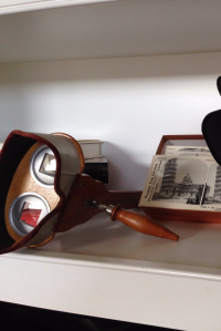 A poorly cropped photo of a stereoscopic viewer with a stereo photo of the Leaning Tower of Pisa in the background.